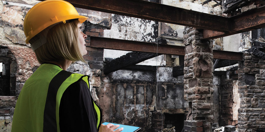 Lady in a helmet looking at fire damage