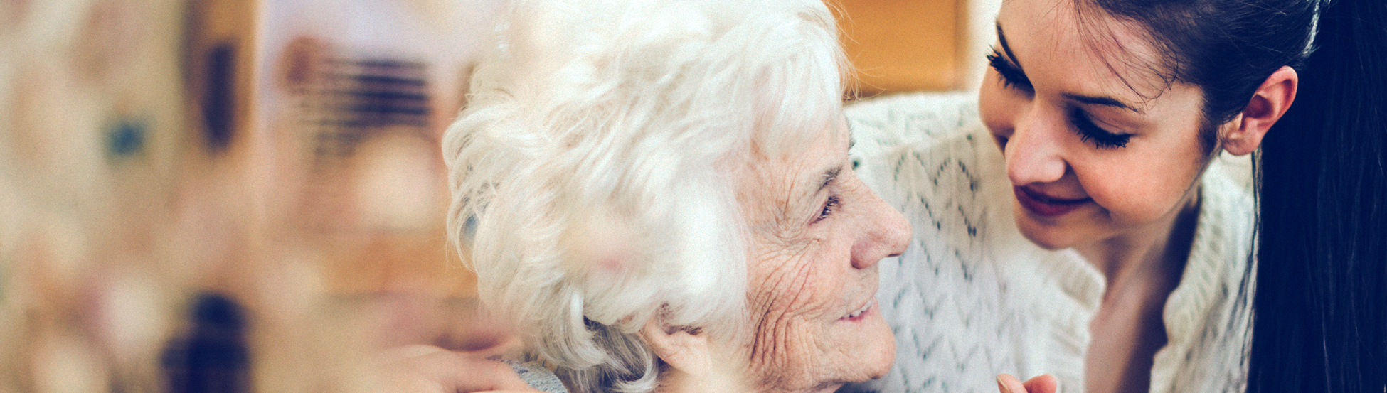 Elderly lady in care home smiling at young female carer