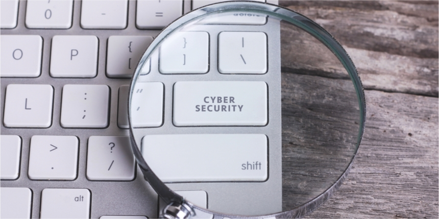 Magnifying glass resting on computer keyboard reading cyber security