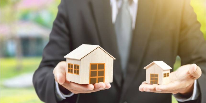 Man in suit holding a house model in either hand