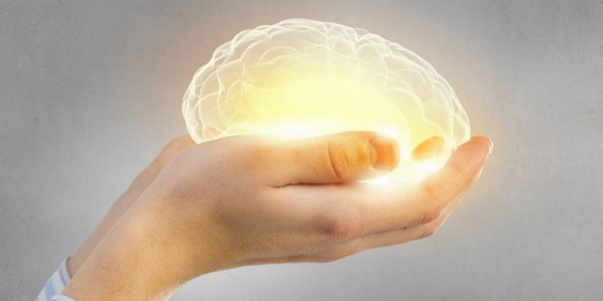 Close-up of hands holding a glowing brain