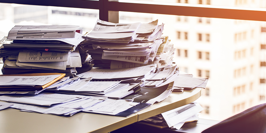 Pile of paperwork on a desk in an office