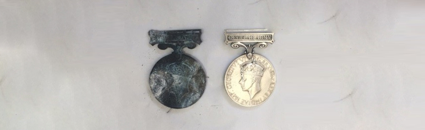 A fire-damaged medal and the same cleaned and restored