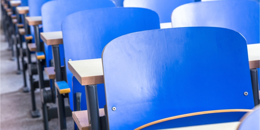 Close up of blue school chairs shown in rows